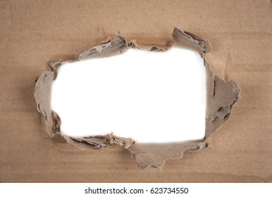 Old brown corrugated cardboard torn and isolated on white. Kraft cardboard goffered. Cardboard ripped edge. Ripped piece of cardboard on white.
