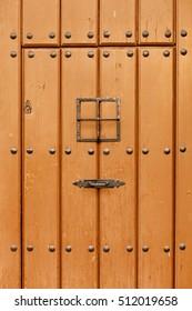 Old brown door with black iron rivets