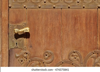 Old brown door with handle and handmade wrought iron details