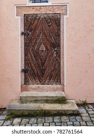 Old brown door from a pink house
