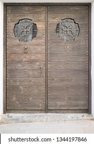 old brown double wooden door decorated with metal and glass