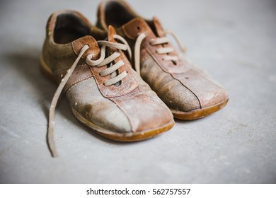 Old brown grunge boots on grey cement background