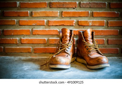 Old brown leather shoes against a brick wall
