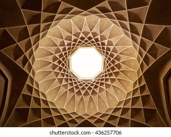 Old brown plasterwork with geometric Persian design inside dome of Governor Pavilion at Dolat Abad Garden of Yazd.