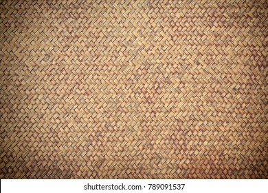 Old brown rattan weave wicker for textured background. Closeup pattern of traditional Thai handmade basket or tray.