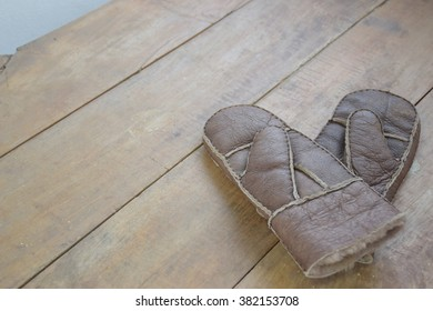 Old brown soft leather mittens on wood table