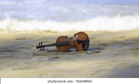 An old brown violin instrument with bow lying in the sand of a beach outdoors