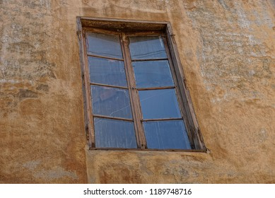 old brown window on the concrete wall of the building