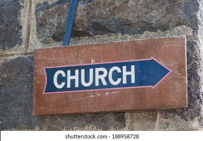 old brown wood church sign with blue arrow on dark stone wall