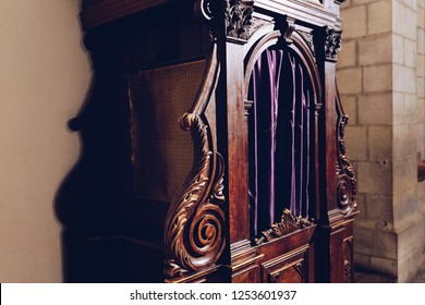 Old brown wooden confessional in the catholic church