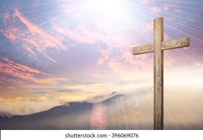 Old brown wooden cross, with sun flash on clouds background