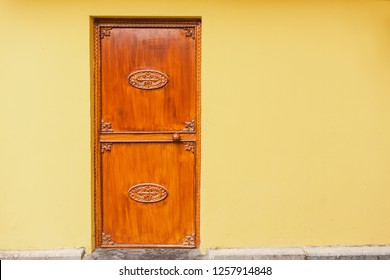 Old brown wooden door in bright orange wall. Horizontal color photography.