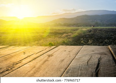 old brown wooden floor beside agricultural field in the evening and beam sunset