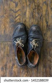 old brown worn men's shoes on a wooden floor