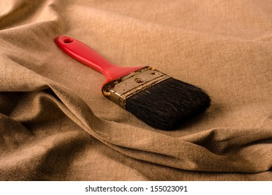 Old brush with red cape in against tissue background.