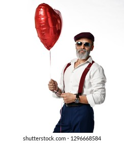 Old brutal senior millionaire man in white shirt and hat in aviator sunglasses stylish fashionable men hold red heart balloon on white background