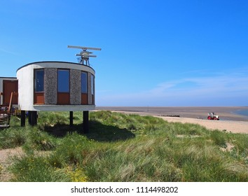 the old brutalist coastguard station in fleetwood with radar antennae with crass covered dunes leading to the beach on a summers day in bright sunlight with blue sky