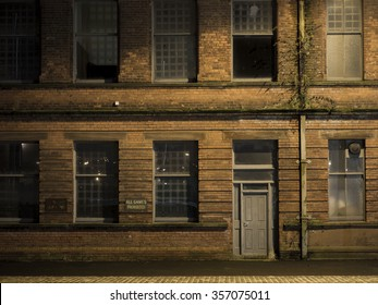 Old building in Belfast docklands with 'No Games Allowed' sign, at night.