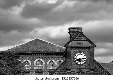 An old building with a clock tower with the clock not working