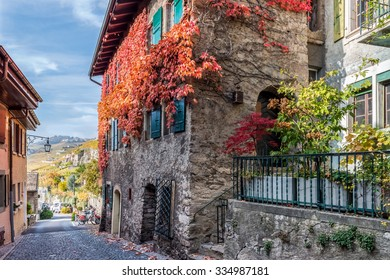 Old building, covered autumn vine rod on the small street of swiss medieval village Saint-Saphorin