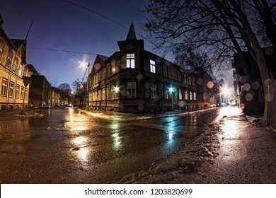 An old building in a crossing on a wet winter night at Tallinn, Estonia. The streets are covered with ice, but it's raining pretty heavily.