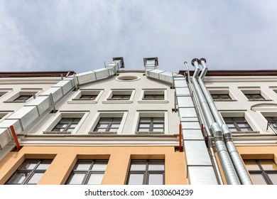 old building facade, bottom view. wall with metal ventilation pipes.