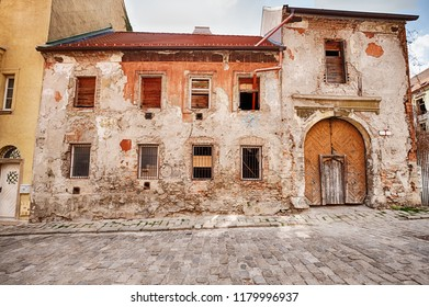 An old building with a large wooden door entrance that is in need of repairs stands next to a street of cobblestones in the Old Town (Stare Mesto) of Bratislava in Slovakia.