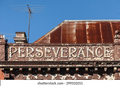 """Old building with peeling paint that says """"perseverance"""""""