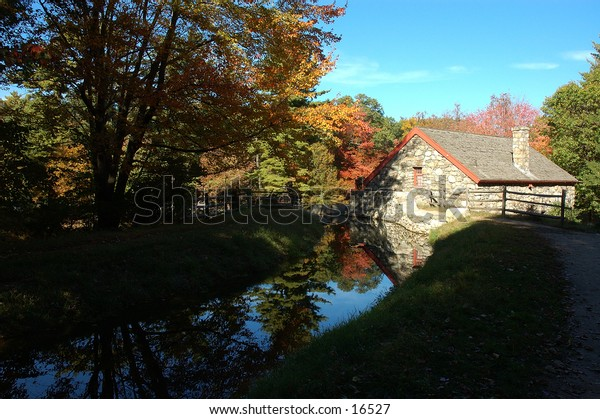 Old building reflected on a stream during an autumn day