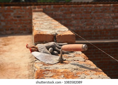 An old building tools, a trowel and gloves lying on a red bricks wall