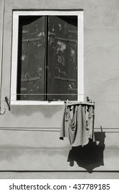 Old building in Venice, Italy. Vintage window with closed shutters and loundry. Black and white photo.