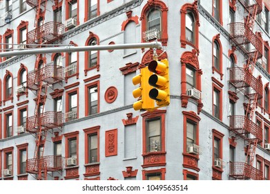 old building with windows with red ornaments in angle of crossroad and yellow traffic light in downtown Manhattan, New York City