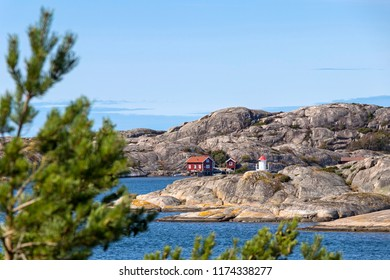 Old buildings or cabins, boats and a little lighthouse at the skerry coast (Sweden). Typical situation for the skerry coast.