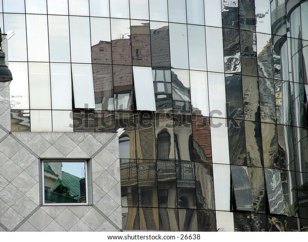 Old buildings reflected in a modern building