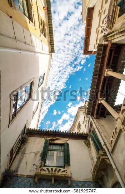 Old buildings viewed from bottom looking up with blue sky during the day in Italy