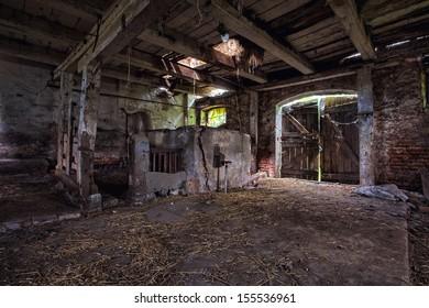 Old, built of wood and brick, abandoned barn.