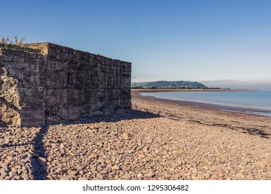 An old bunker on the beach in Blue Anchor, Somerset, England, UK - looking at the Bristol channel and Minehead in the background