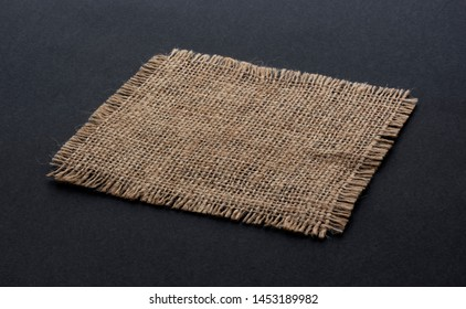 Old burlap fabric napkin closeup. Rough linen jute, sackcloth piece isolated on black background. Hessian texture cloth tag with frayed edges. Dark sack material