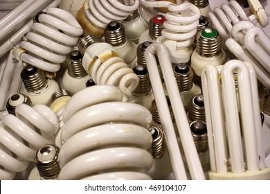 Old burnt fluorescent energy saving lamps. Hazardous and toxic electronic waste