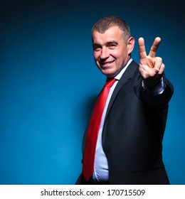old business man making the victory hand sign on blue background