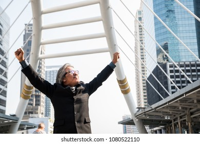 A old businessman is proud for the  successful of company and his job. Hand up in the air and feeling powerful. City background.