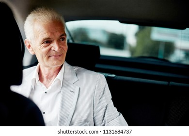 Old bussines man sitting in the car and look around and smilling. Thinking about new possibilities.