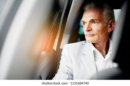 Old bussines man sitting in the car and look around. Thinking about new possibilities.