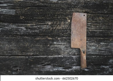 Old butcher knife full of rust.That is on wood background.