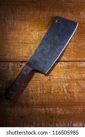 Old butcher's cleaver on a wooden desk