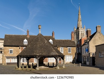 Old Buttercross in Oakham Town market place with buildings of Oakham School behind, Rutland, England, UK