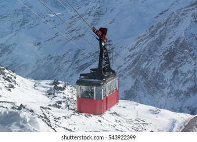 Old cable car transports people on a background of mountains and snow in the ski resort, Mount Elbrus, Azau