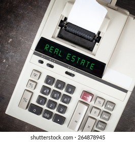 Old calculator showing a text on display - real estate