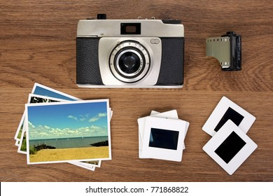 Old camera, mounted film slides and photo's on wooden background