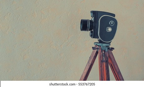 The old camera on a wooden tripod stands on a background of a wall